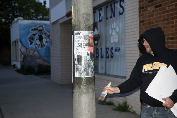 "Postering for Stories to the Streets:  Vita Brevis, Ars Brevis"" part of Mayworks Windsor 2016.  Photo:  Doug MacLellan."
